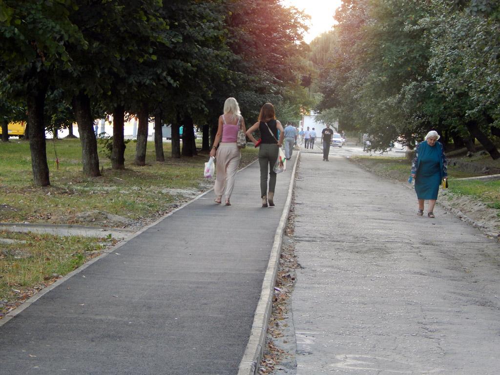 Група людей, які йдуть вниз по тротуару