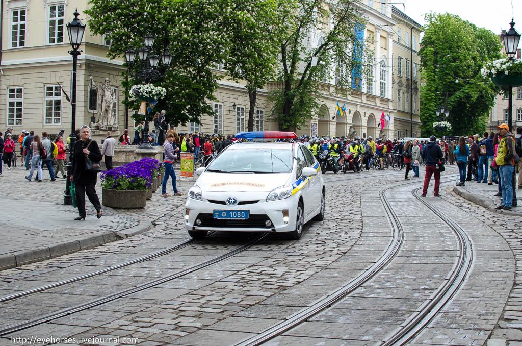Група людей, які йдуть вниз по тротуару поруч з автомобілем