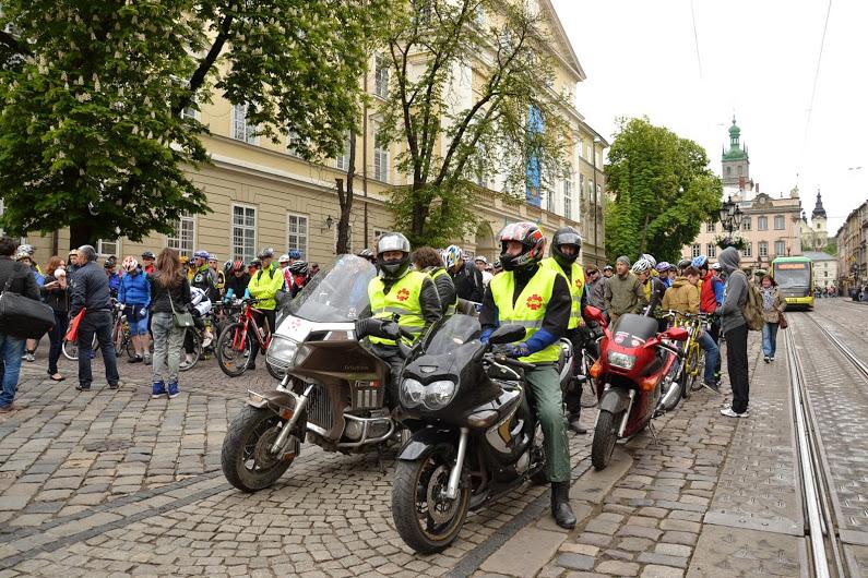 Група людей на тротуарі поруч з мотоциклом