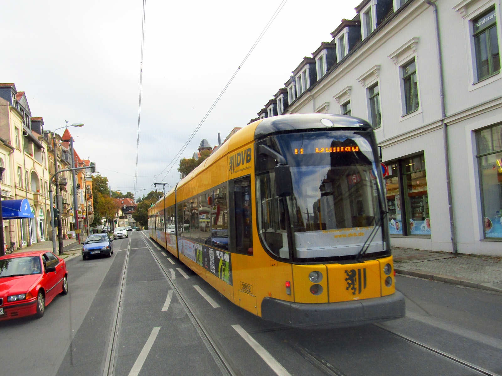 Жовта автобусна проїжджаючи вниз по вулиці