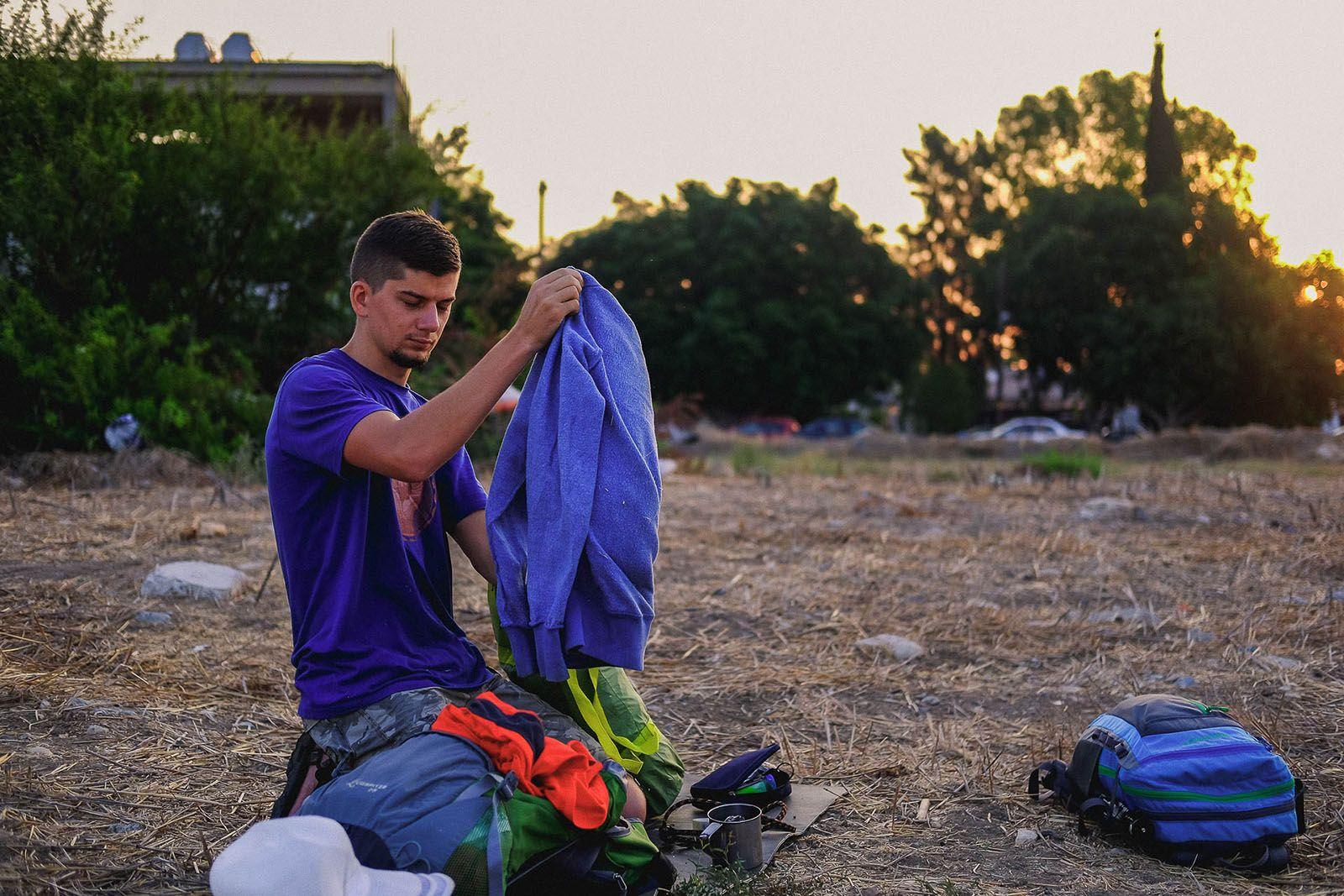 Волоцюга збирає свої речі після ночівлі