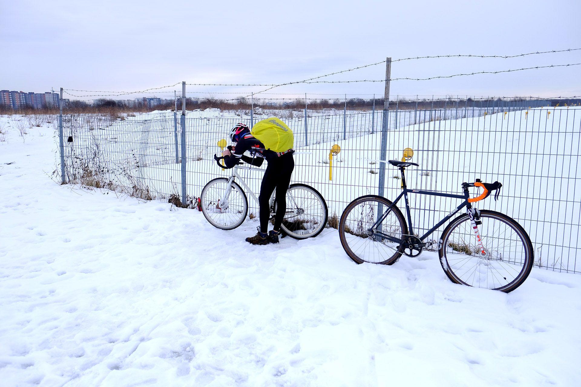 Чоловік з велосипедом в снігу