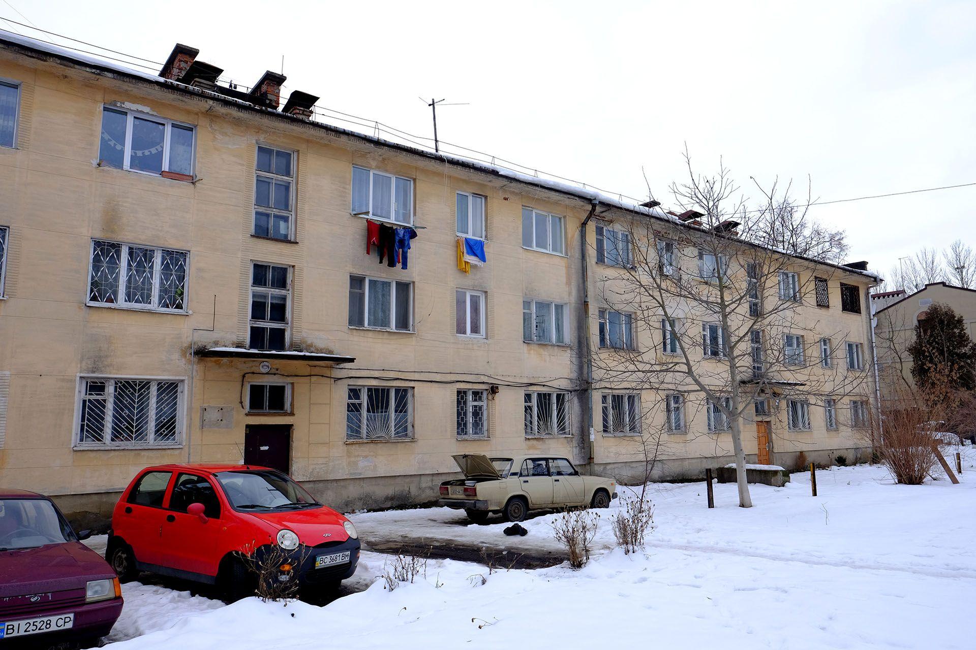 Автомобіль, припаркований перед будинком, вкрите снігом