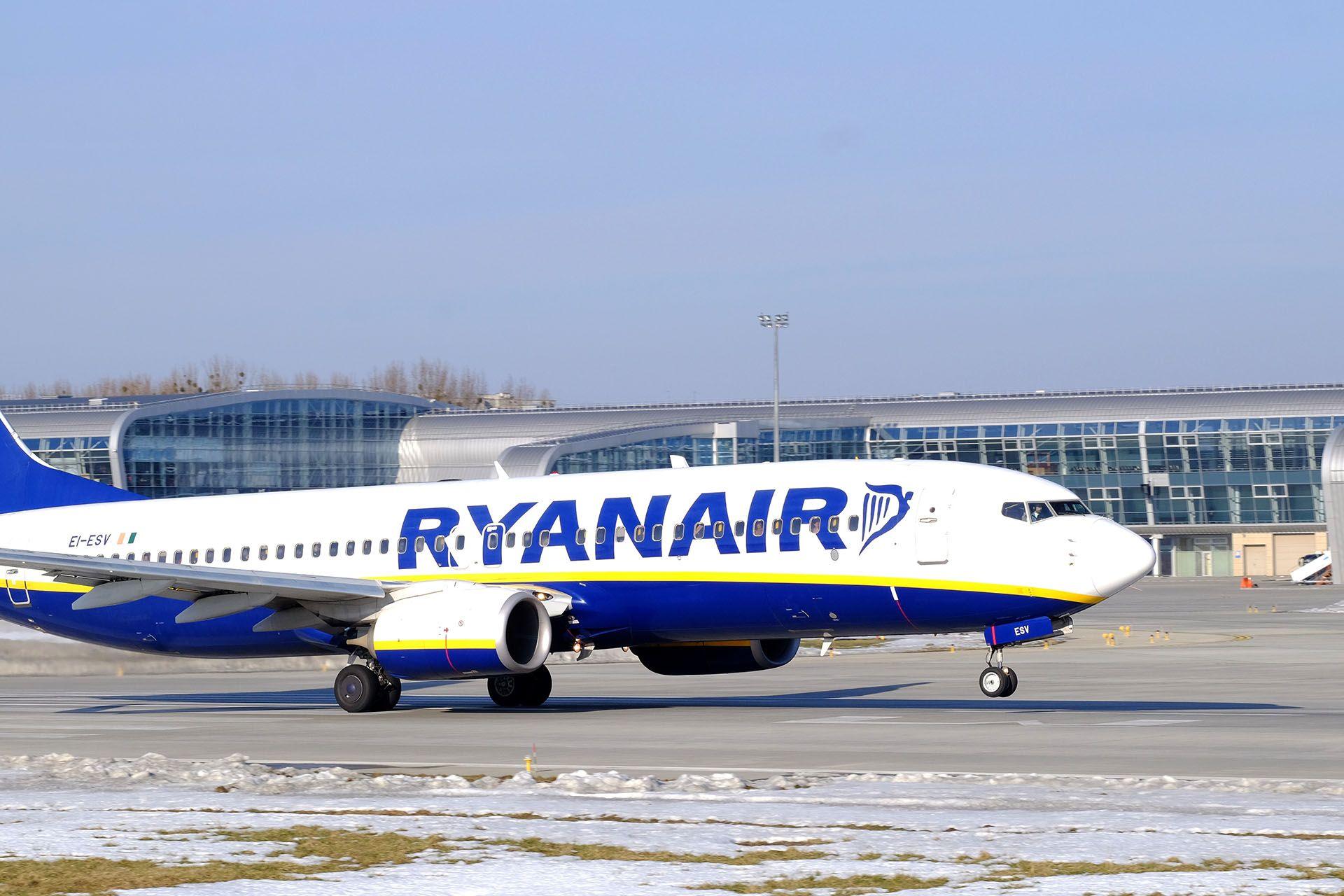 Синьо-білий літак на злітно-посадковій смузі в аеропорту