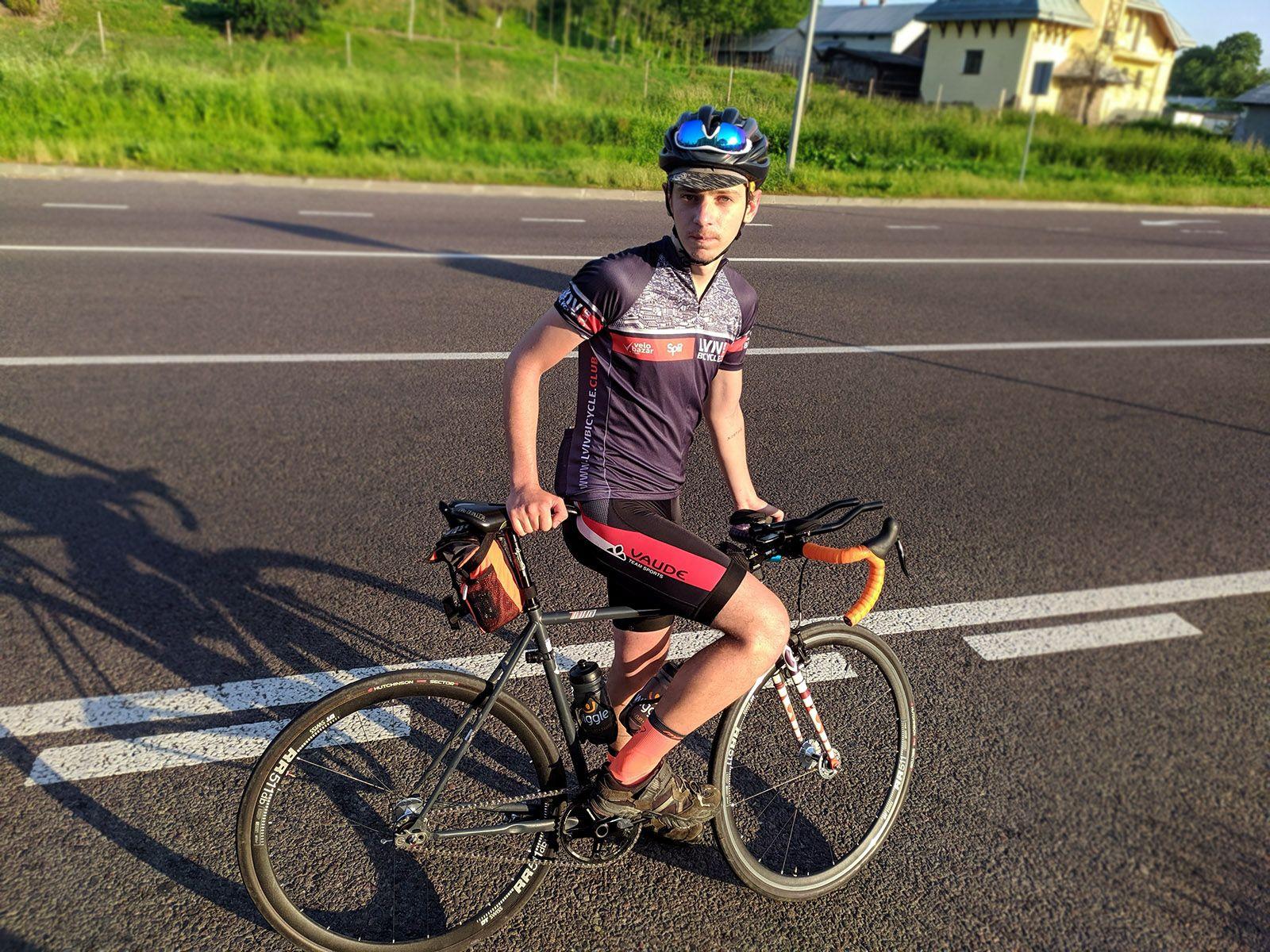 Особа, яка їде на велосипеді збоку дороги