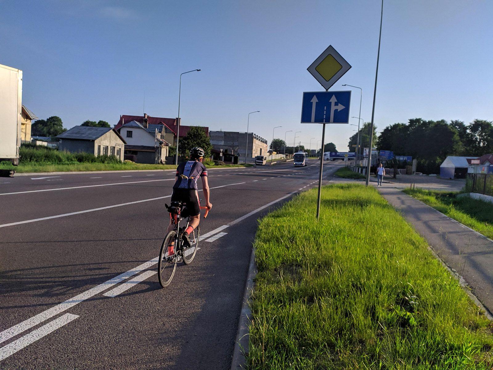 Чоловік їде на велосипеді збоку дороги
