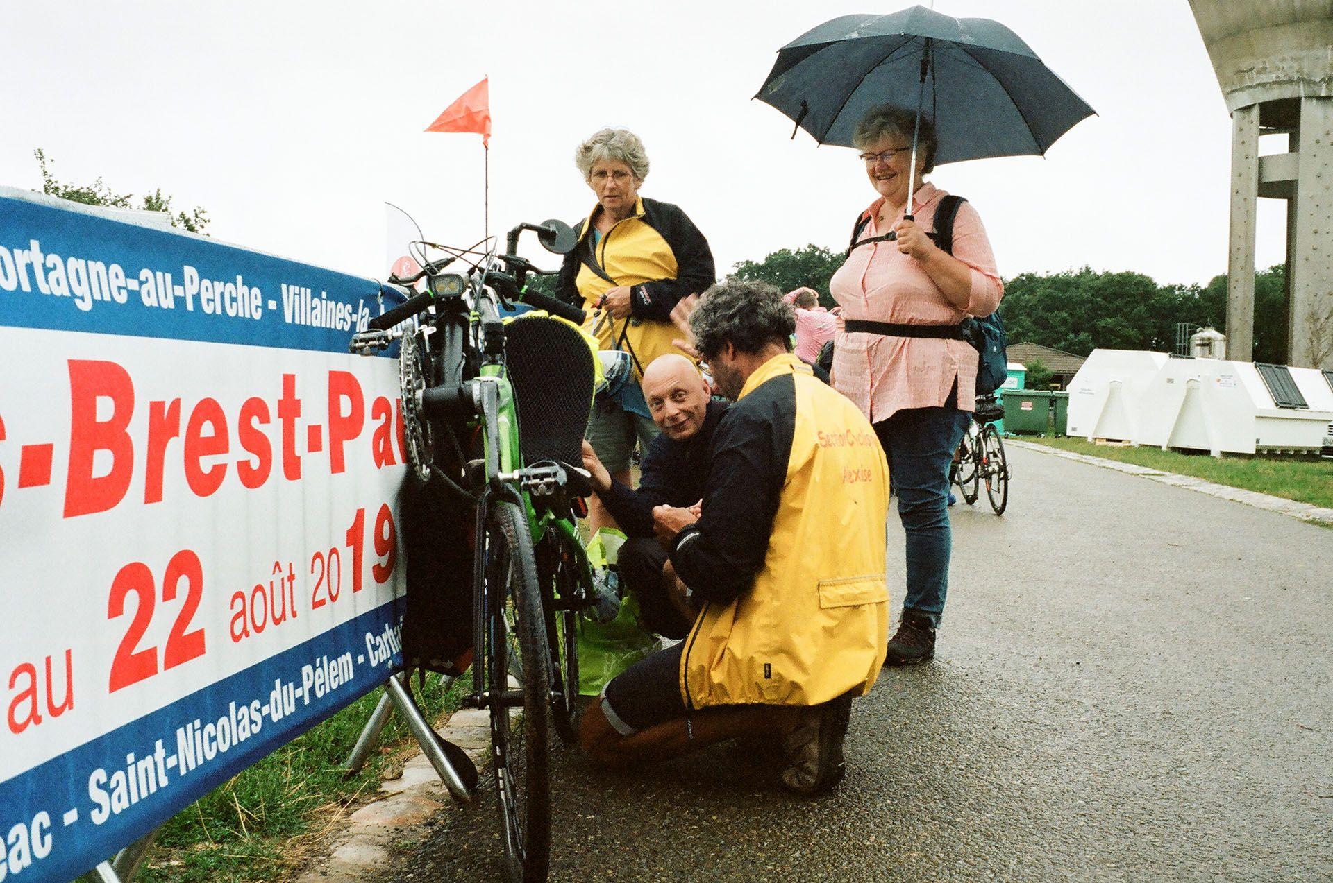 Старший чоловік разом із друзями роздивляється свій велосипед після байкчеку