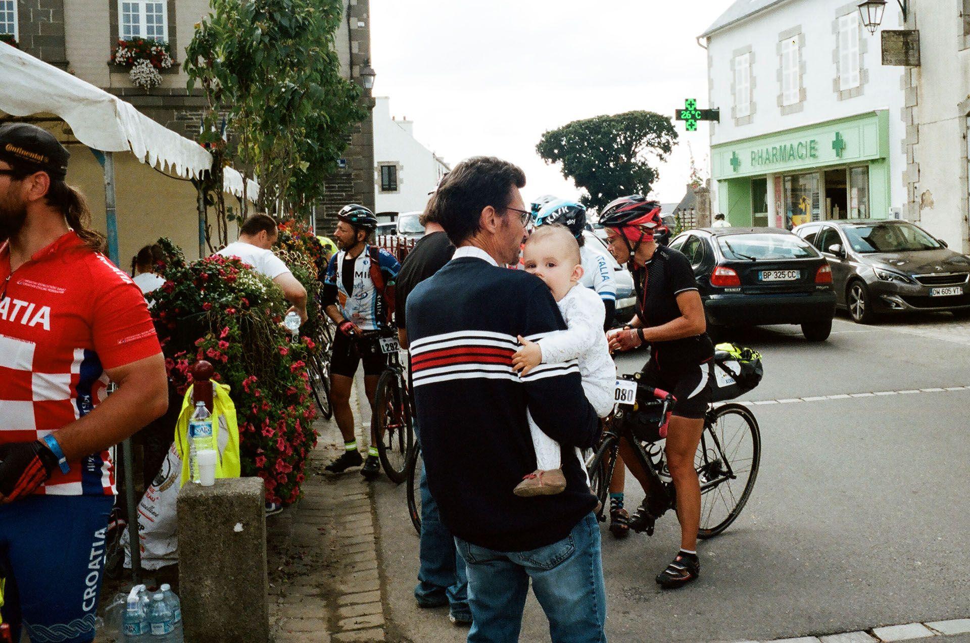 Батько із маленьким сином спостерігають за учасниками марафону