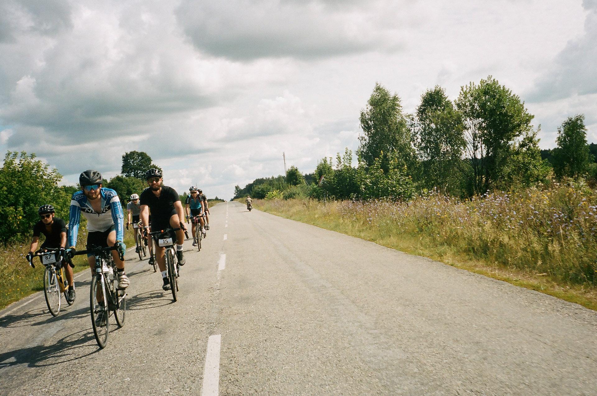 Група людей верхи на конях на грунтовій дорозі