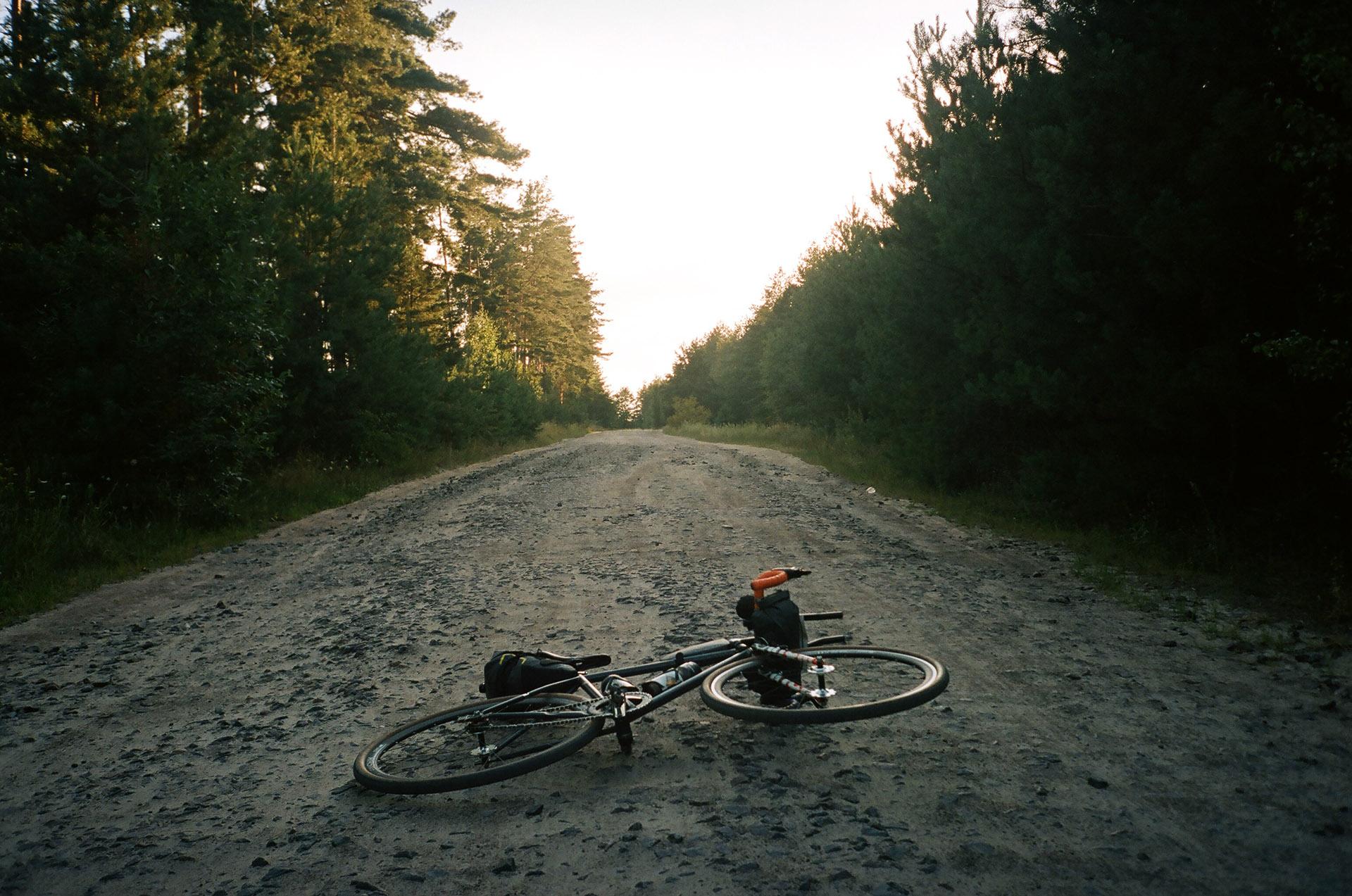 Людина їде на мотоциклі вниз по грунтовій дорозі