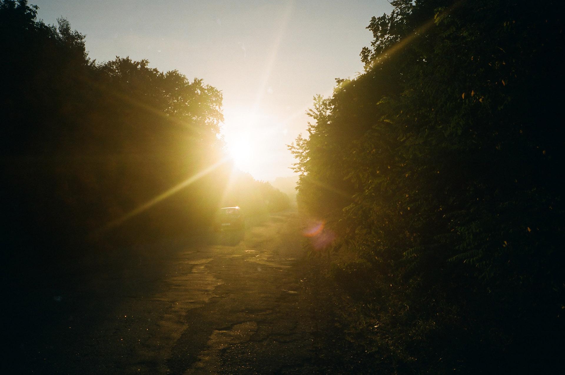 Чоловік із заходом сонця на задньому плані