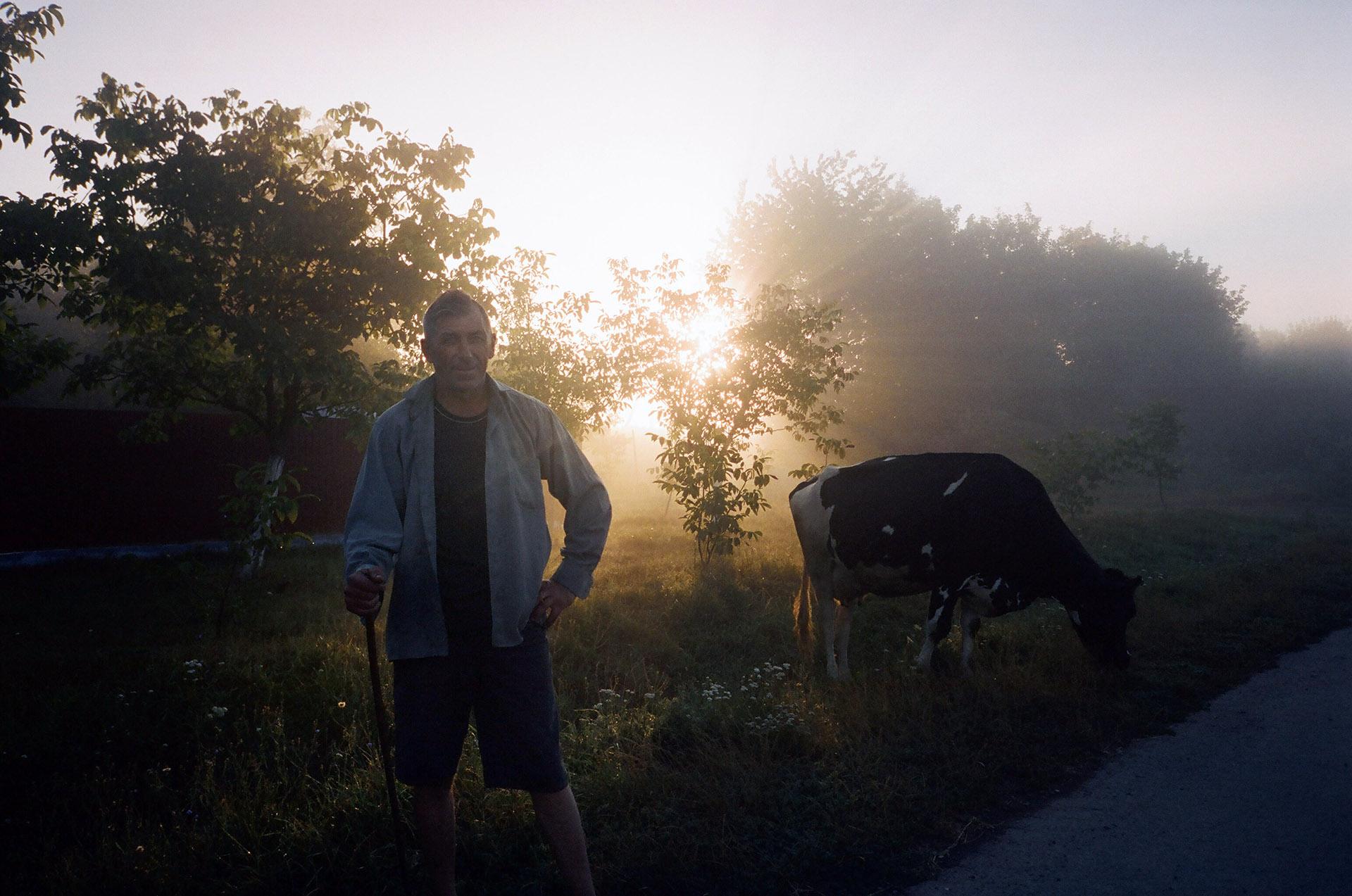 Чоловік, що стоїть поруч з конем у полі