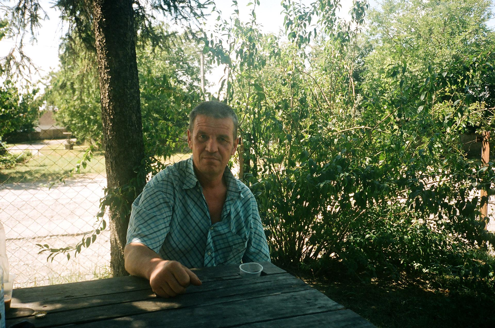 Чоловік сидить на лавці перед деревом