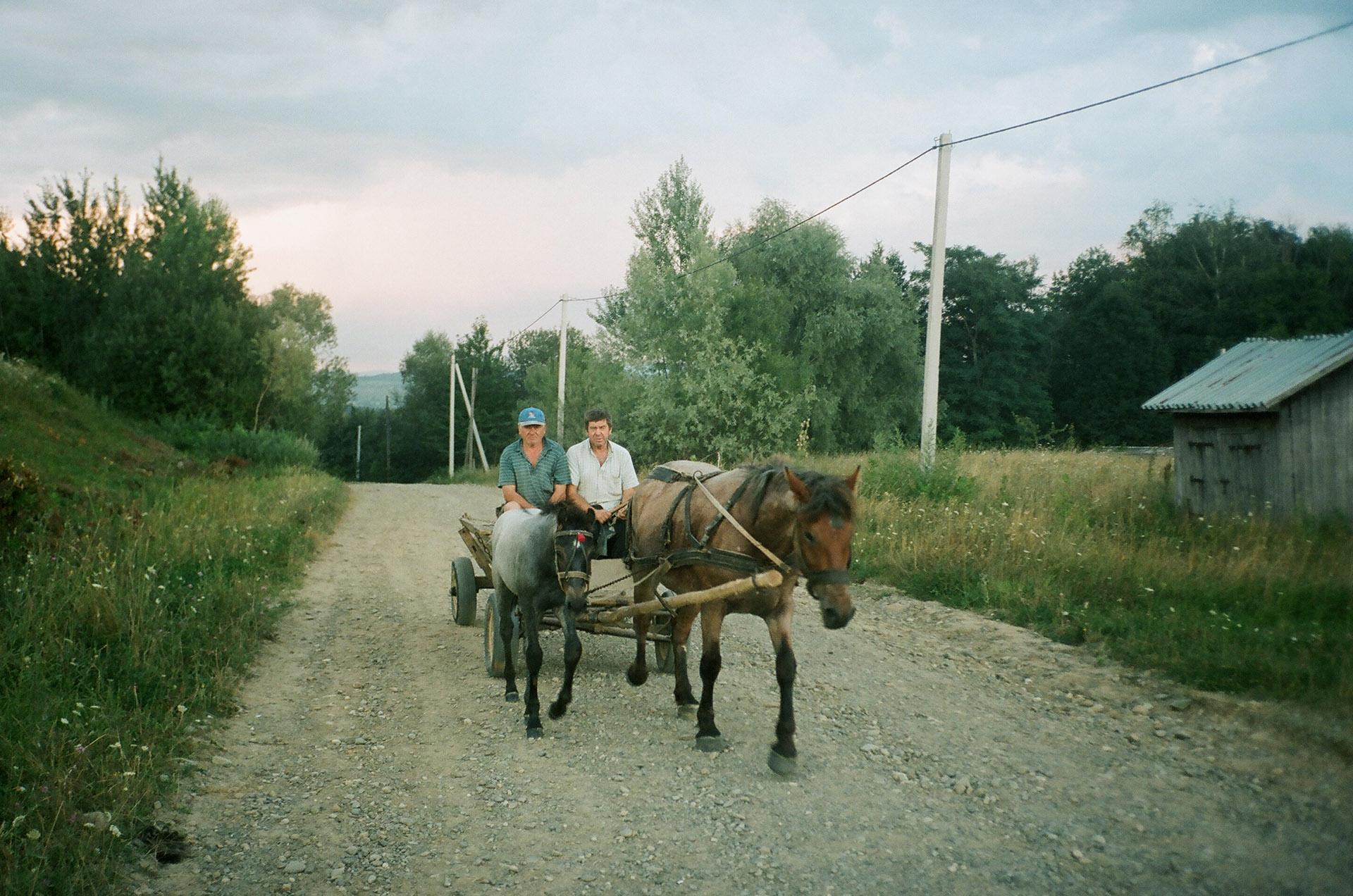 Людина, що їде на коні, намальована коляскою, що подорожує по грунтовій дорозі