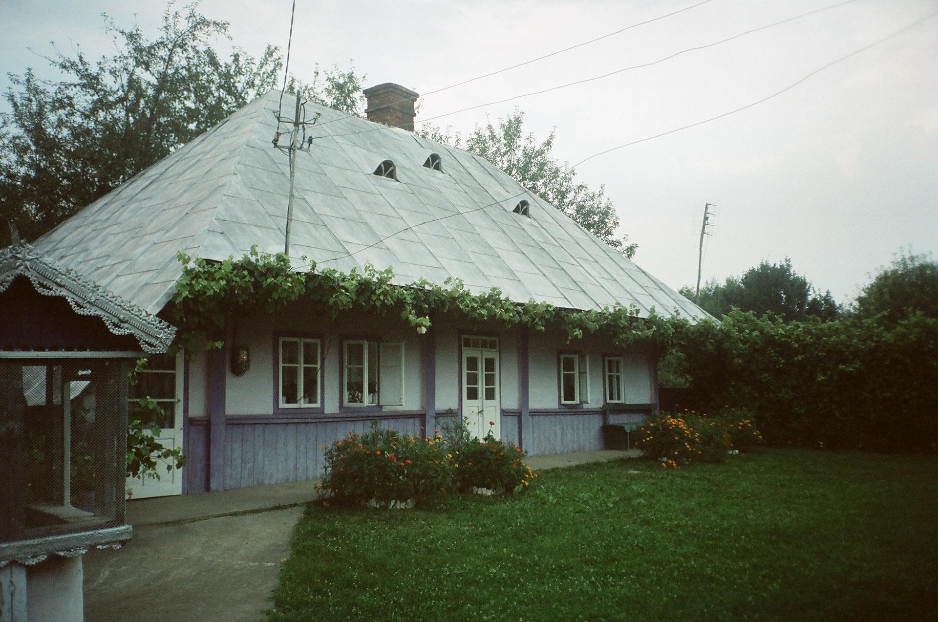 Велика цегляна будівля з травою перед будинком