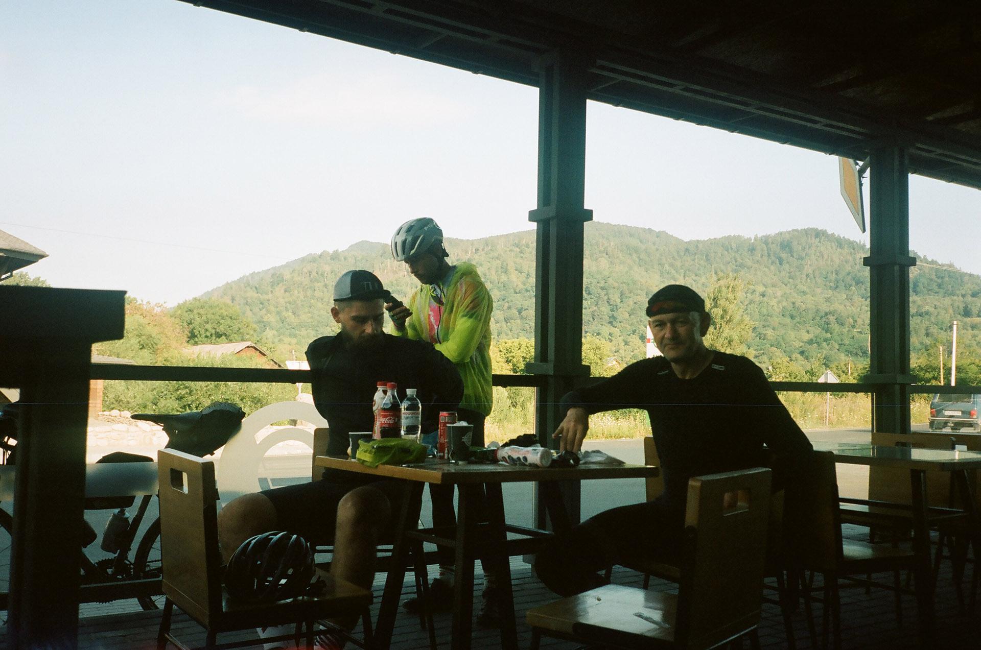 Група людей, які сидять за столом перед вікном