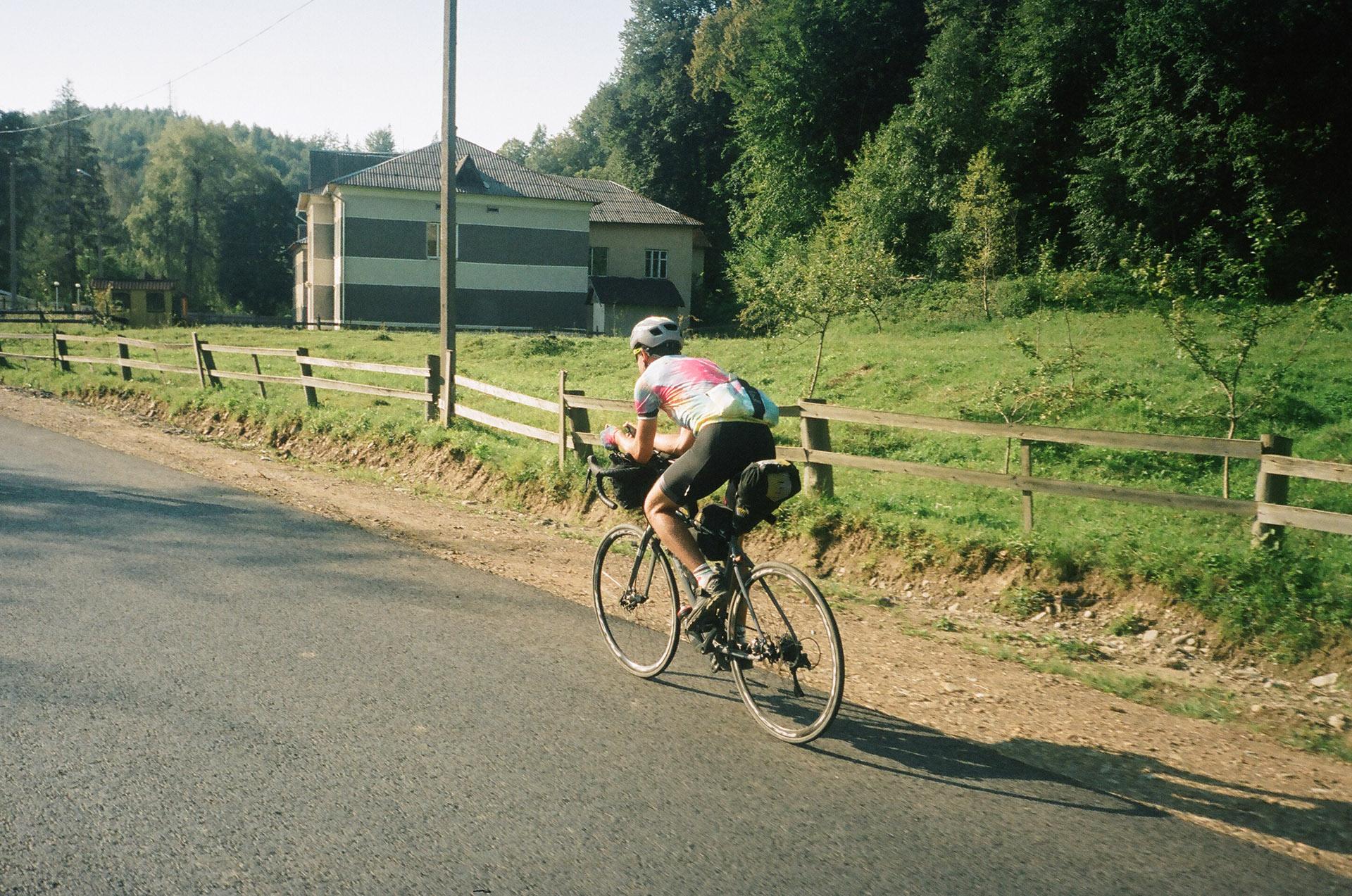 Людина, що їде на велосипеді вниз по грунтовій дорозі