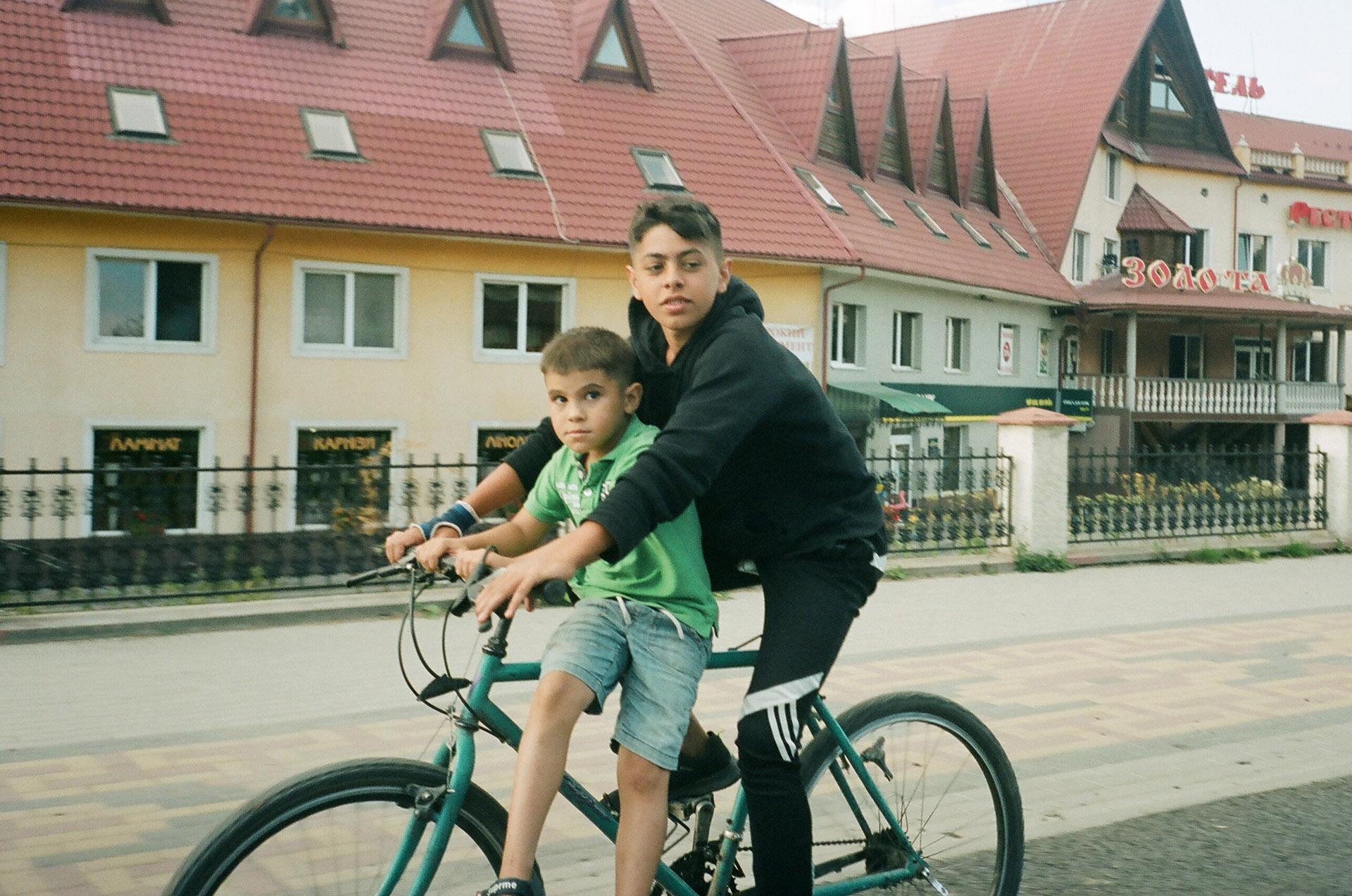 Молодий хлопець їздить на велосипеді перед будівлею