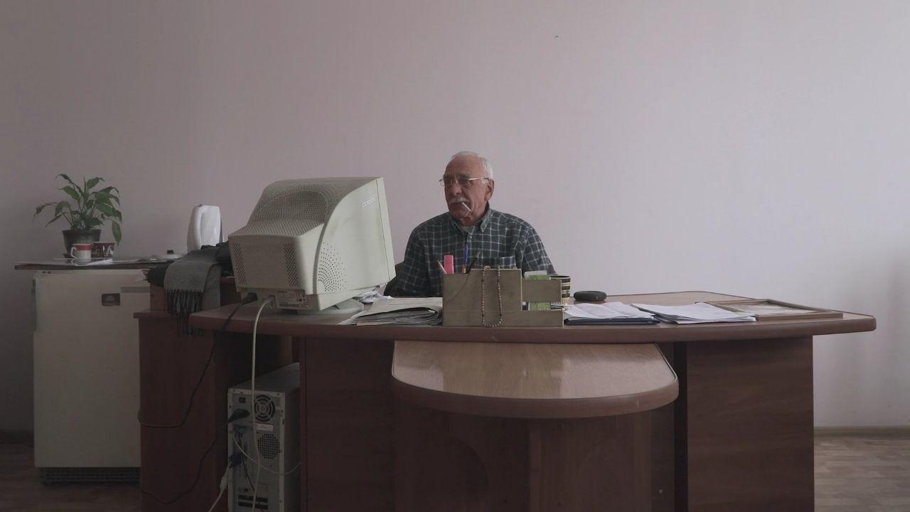 Людина, яка сидить за столом з ноутбуком