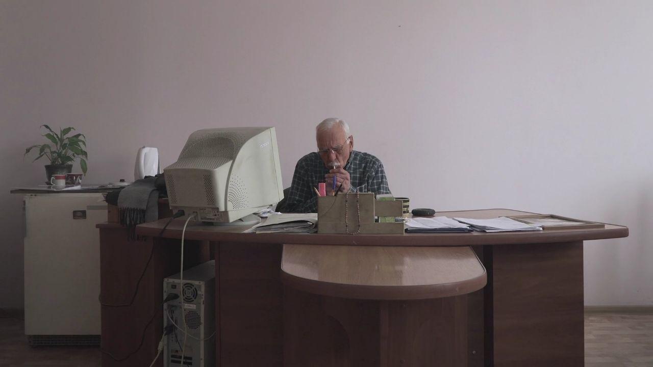 Людина, яка сидить за письмовим столом