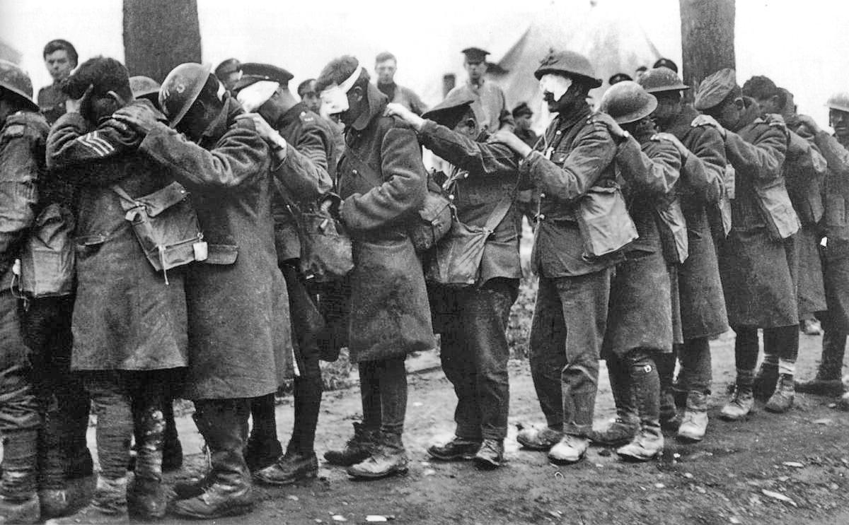 Blinded by gas, British soldiers of the 55th division hold onto each other at an Advanced Dressing Station