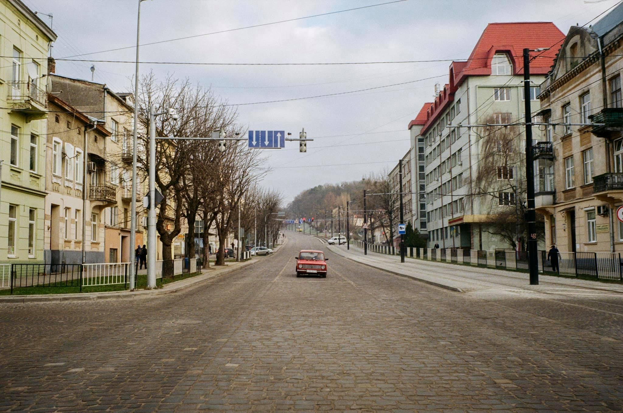 Вузька міська вулиця з автомобілями, припаркованими на узбіччі дороги